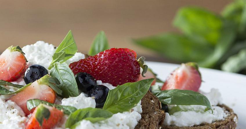 Meergranenbrood met hüttenkäse, aardbeien en bosbessen